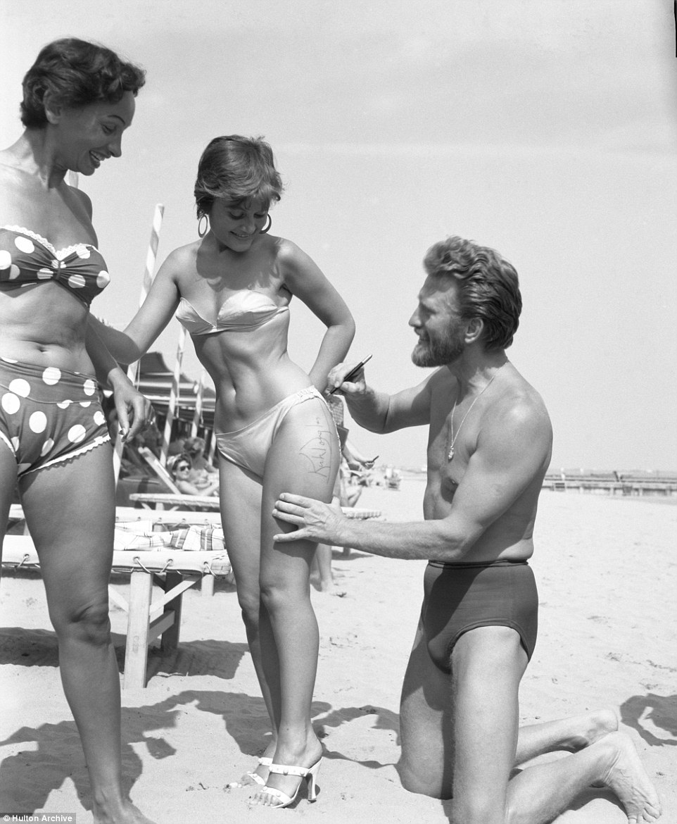Glamorous riviera: American actor Kirk Douglas, wearing just a swimming suit, signing the thigh of the painter Novella Parigini while another woman looks on at Lido Beach in 1953