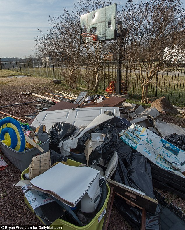 The once luxurious property now looks scruffy and neglected and junk is piled up in the yard  - the basketball hoop is a sad reminder of the former NBA star's glory days