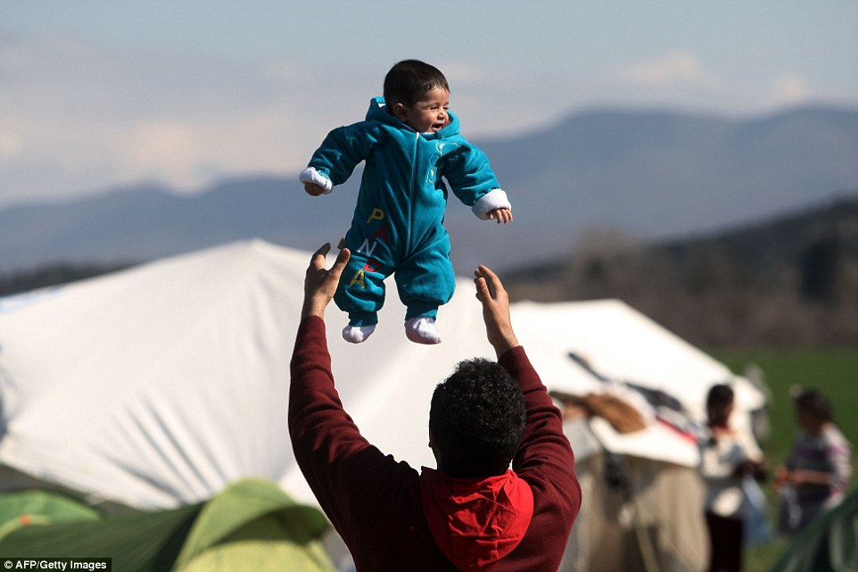 Light relief: A migrant plays with his child as migrants and refugees wait to cross the Greek-Macedonian borde