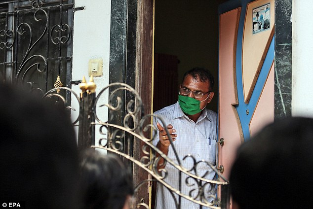 A police investigator wearing a face mask leaves the house where the chartered accountant slit his relatives throats