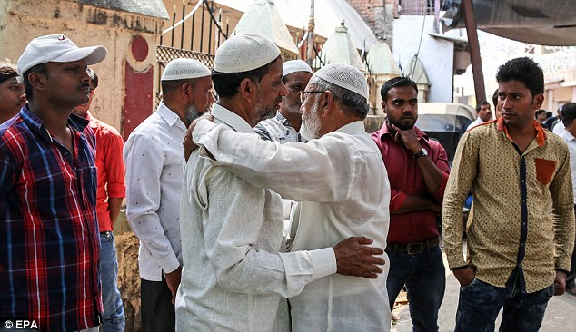 Local people and other residents gather to mourn outside the house whereHasnin Anwar Warekar killed 14 of his family members before killing himself