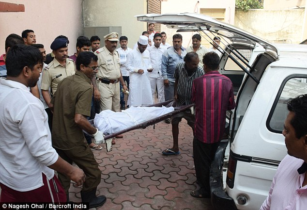 A body is carried out of the hospital after an autopsy. The lone survivor of the attack was Warekar's 21-year-old sister
