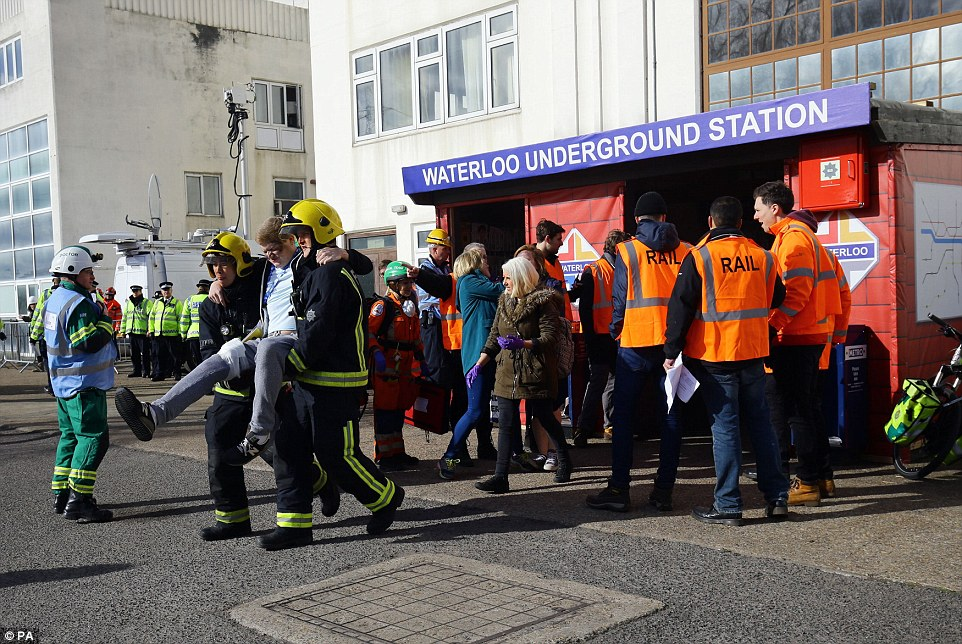 Treatment: Firefighters carry out one actor who was left unable to walk after he 'injured' his leg in the Tube station collapse