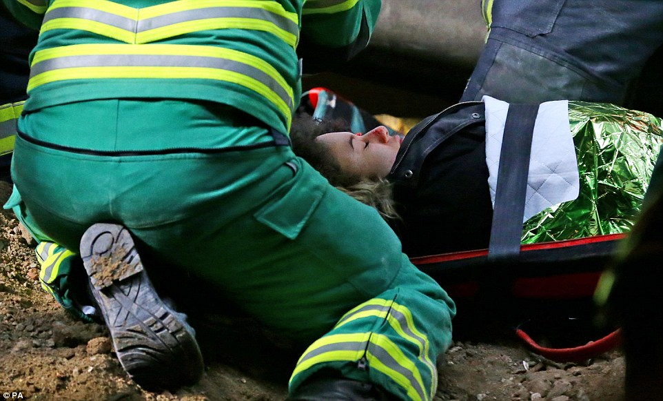 Carried to safety: A volunteer playing a woman injured in the collapse is strapped to a stretcher before being taken out of the station