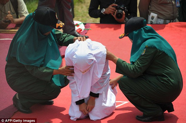 Two  policewomen help the teenager after she received a caning  during a public punishment in Banda Aceh