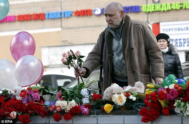 Tributes: A man leaves a flower site near the Oktyabrskoye Pole underground station in Moscow, Russia