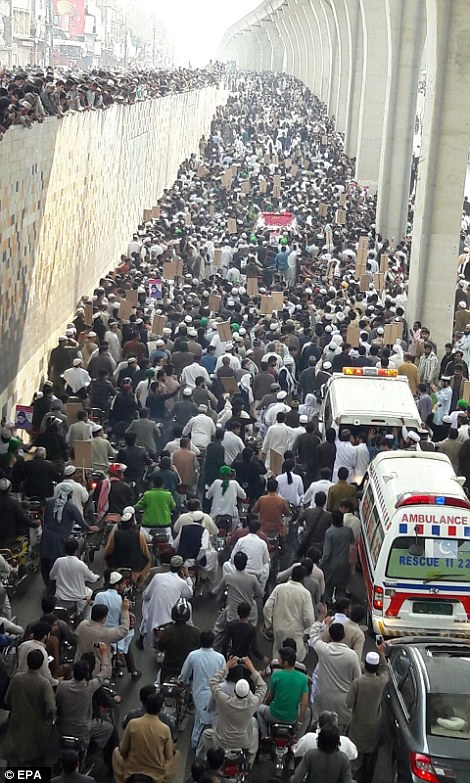 The ambulance carrying Qadri's body winds its way through the city streets