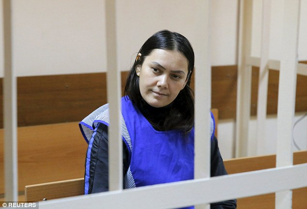 Gyulchekhra Bobokulova sits inside a defendants' cage as she attends a court hearing in Moscow