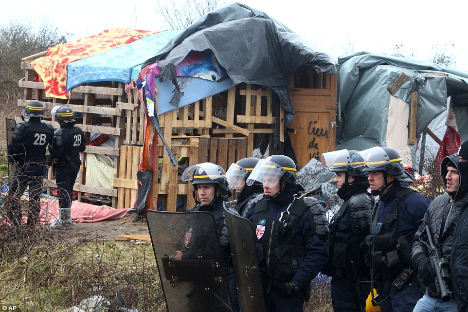 French riot police secure an area where French officials tell migrants they must leave in a makeshift migrants camp near Calais, France