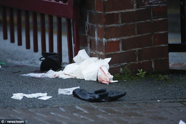 A glove, pictured, and blood stained medical supplies remain on the floor outside the church following Friday's incident