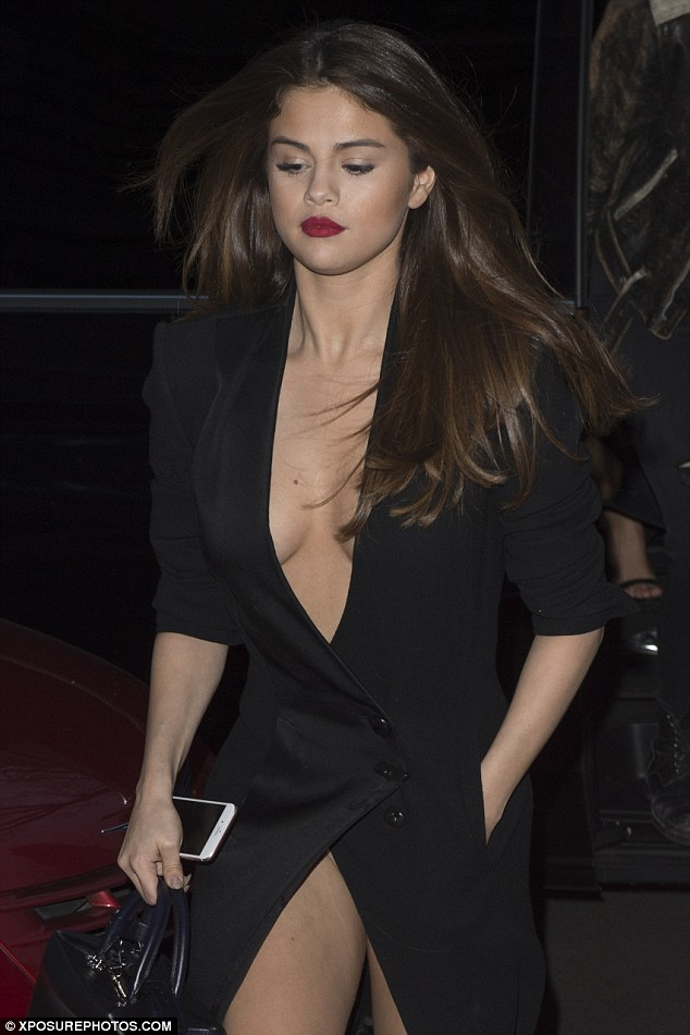 Daring to bare: Selena opted to forgo a bra in her rather racy dress, held together by a few buttons at the waist