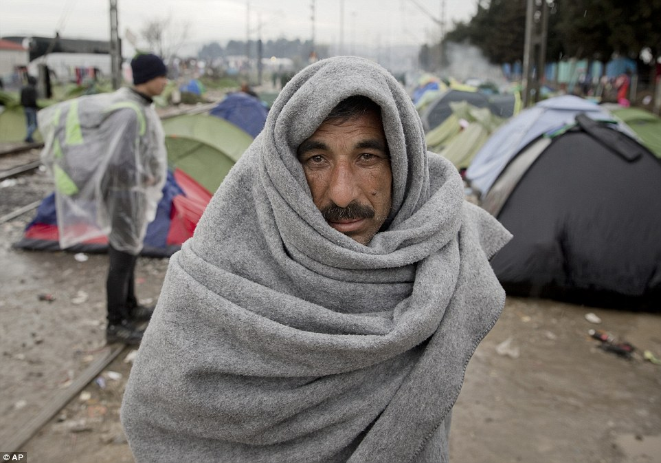 A migrant covers himself in a blanket during rainfall at the northern Greek border station of Idomeni. Despair and confusion spread through the camp at the Greek-Macedonian border as thousands of stranded refugees were forced to acknowledge the Bakan route was now shut
