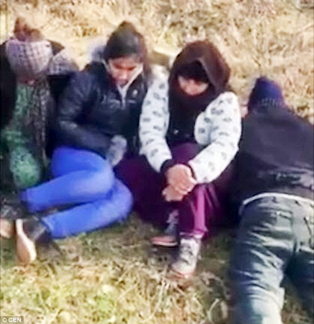 Huddled in fear: Suspected illegal migrants cower on the ground after being 'caught' by Valev. Human rights activists have accused Valev of terrorising his captives with death threats