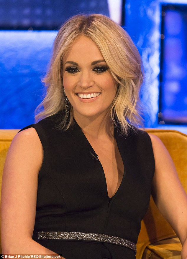 Blonde bombshell: Singer Carrie Underwood looked gorgeous in a plunging black top, featuring a silver band