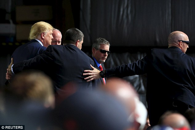 The Secret Service agents then form a protective shield around Trump after someone tried to jump the barrier