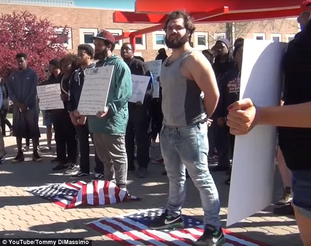 Students, including Dimassimo, were then recorded and photographed (above) standing on American flags and holding signs saying, 'Not my flag'