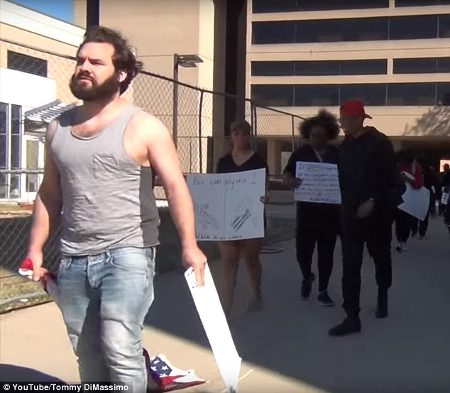 While at the protest, Dimassimo, who is originally from Powder Springs, Georgia, was recorded on camera dragging the American flag (above)