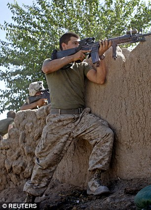 Staff Sergeant William Bee, without wearing a helmet or Kevlar vest, aims at a window from where he feared a Taliban sniper was positioned