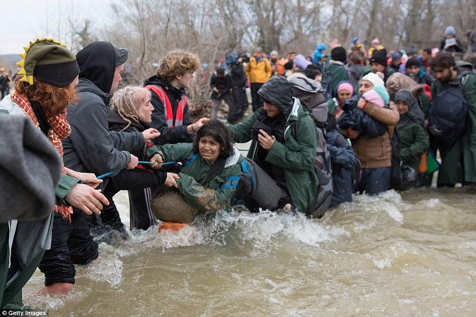 Peligrosa: inmigrantes desesperados que se dirigían a Macedonia, después de abandonar el campo de refugiados Idomeni en Grecia, se ven obligados a cruzar un río mientras que agarra sus pertenencias y niños pequeños