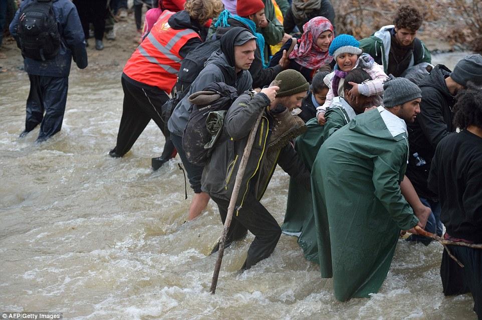 Los voluntarios acamparon en ayudar a los migrantes cruzan el río y un hombre se puede ver sosteniendo un bastón ya que ayuda a otro llevar a un niño migrante a la seguridad