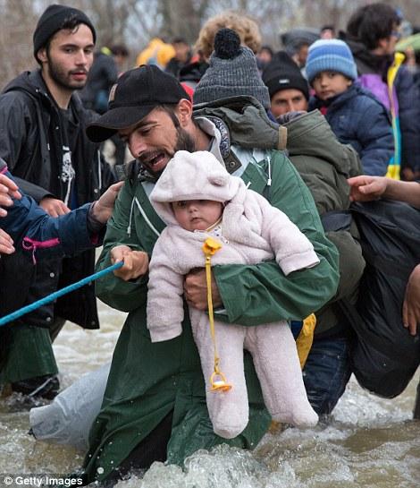 En la foto, un padre se aferra a su bebé, ya que hacen el viaje peligroso cruzar el río en Grecia con otros cientos de personas