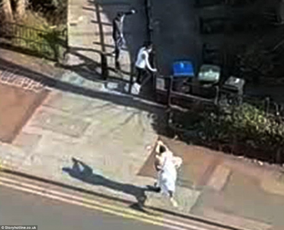 A gunman who appeared to be wearing Muslim dress was filmed chasing four teenagers past houses and parked cars before allegedly trying to shoot one of them as they cowered next to a house