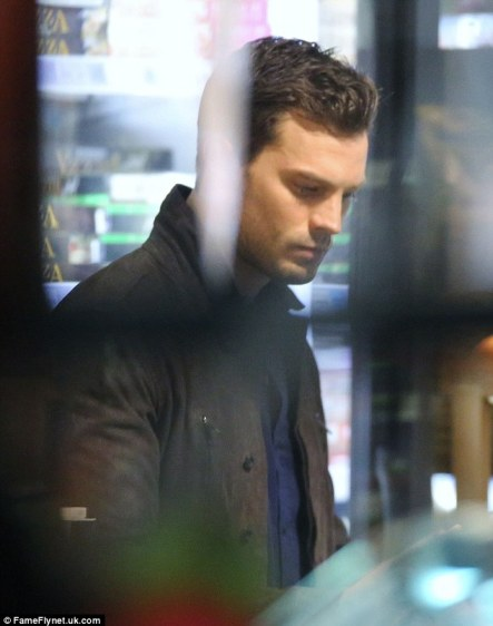 Contemplative: Actor Jamie Dornan, 33, portrays billionaire misogynist Christian Grey in the film. He appeared lost in thought as he exited a grocery store wearing a blue button up and a grey coat