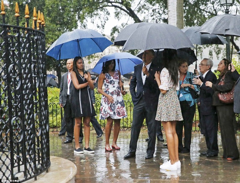 Rain on their parade: The Obamas looked less than impressed by the rain as it came down hard on them while they toured Old Havana after landing in Cuba on Sunday evening