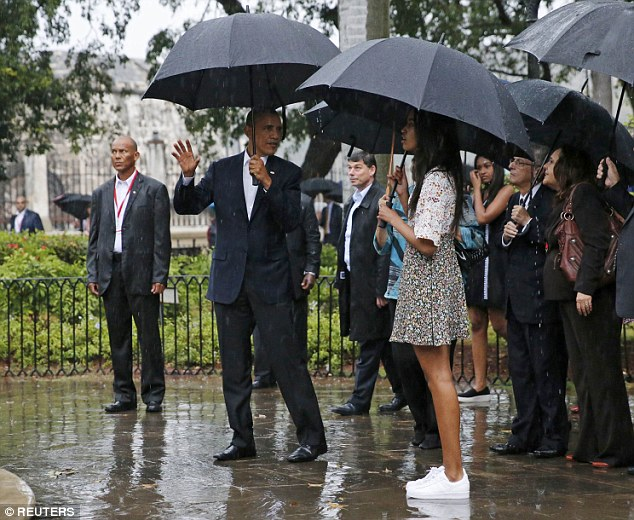 The president appeared to be explaining something to his daughter Malia as they were guided around Old Havana on a rainy evening