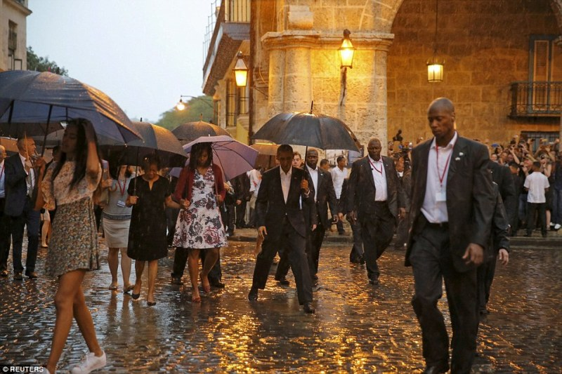 President Barack Obama steps over a puddle as he and his family tours the cobbled streets of Old Havana, despite the rain