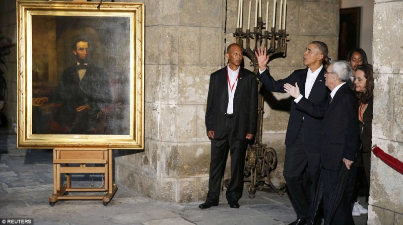 U.S. President Barack Obama stands near a portrait of Abraham Lincoln rolled out just for his visit as he is guided on a tour of the Museum of the City of Havana