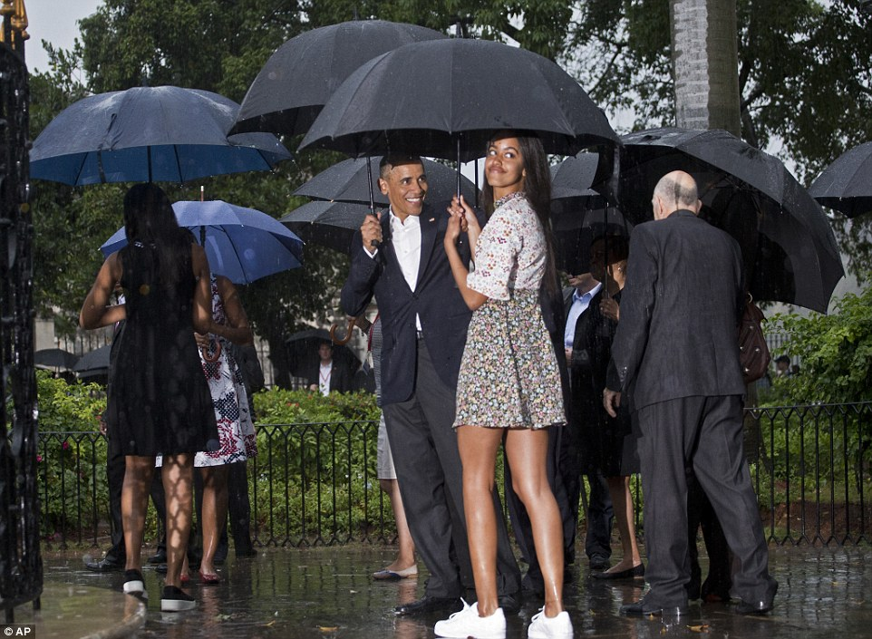 Family outing: The first family pressed on, despite the stormy skies, strolling through the Plaza des Armas as they huddled under their umbrellas as they made their way to the Museo de la Ciudad, the museum of the Cuba's capital city