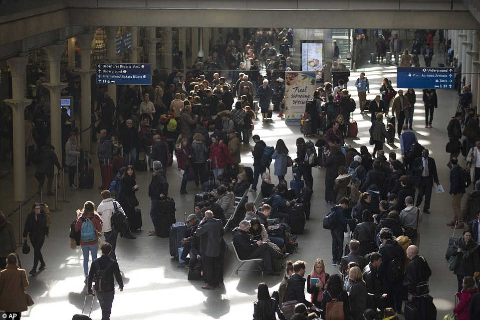 Travellers stand in a long queue at St Pancras station in London, after all trains in and out of Brussels were suspended this morning