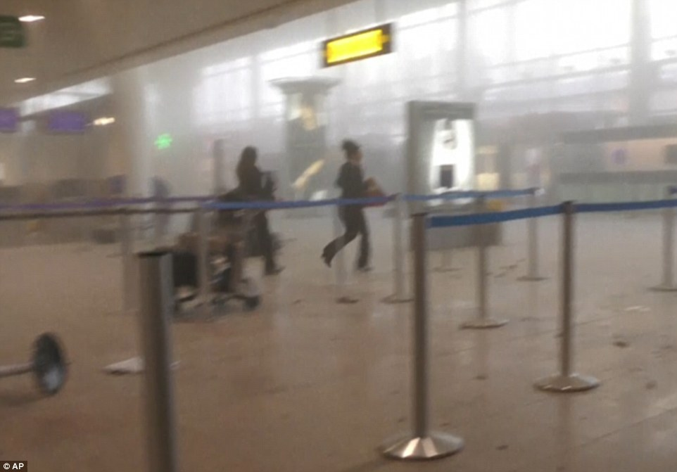 Terrified passengers run for their lives in a cloud of smoke moments after the explosions ripped through the terminal