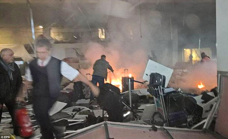 Panic: A fire caused by one of the explosions in the terminal is tackled by airport staff with extinguishers surrounded by baggage and falling roof tiles