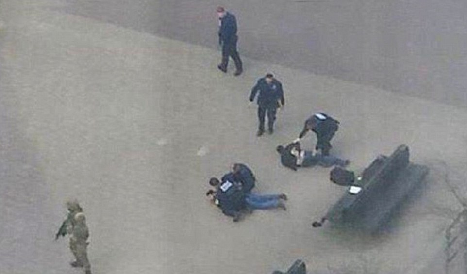 Drama: Two men were pinned to the ground by armed police and special forces as the hunt for members of the terror cell behind today's bombings in Brussels started