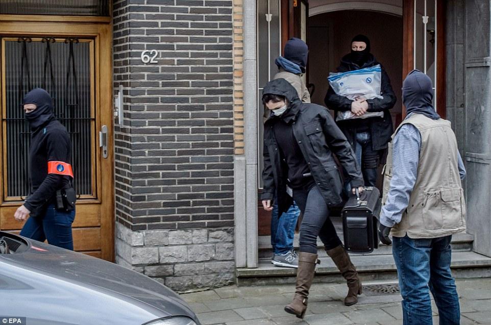 La recopilación de pruebas: la policía forense dejar una casa en el distrito de Anderlecht en Bruselas, mientras que otros llevan evidencia encontrada durante una incursión