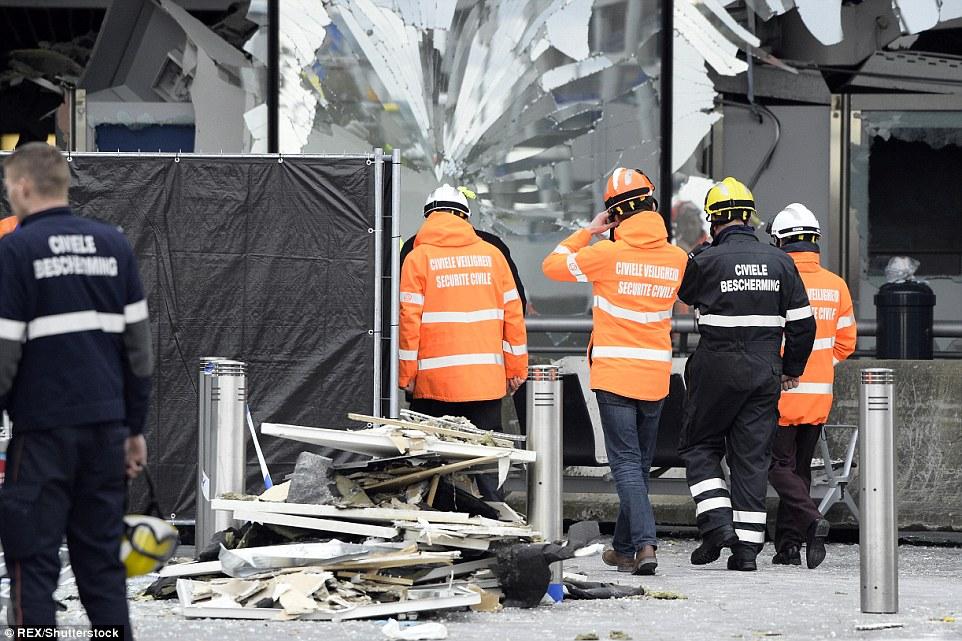 Escombros y desechos: Los funcionarios de seguridad, ingenieros y trabajadores de servicios de emergencia estaban trabajando duro en el aeropuerto de Bruselas esta tarde