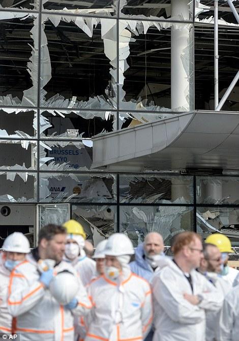 oficiales de análisis forense de pie delante de la dañada terminal de aeropuerto de Zaventem, en Bruselas