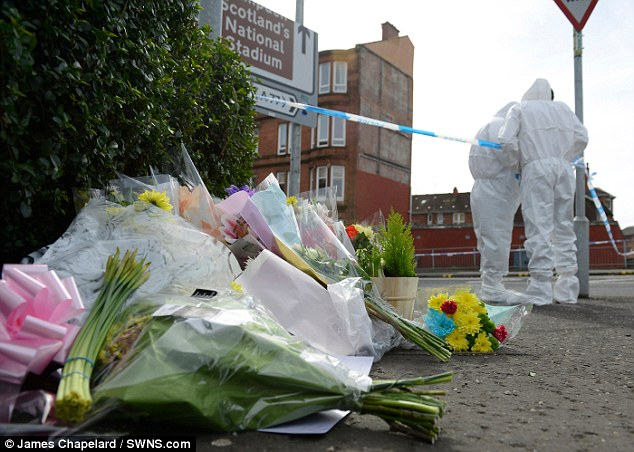 Forensics personnel sweep the murder scene as tributes and flowers begin to pile up next to a police cordon