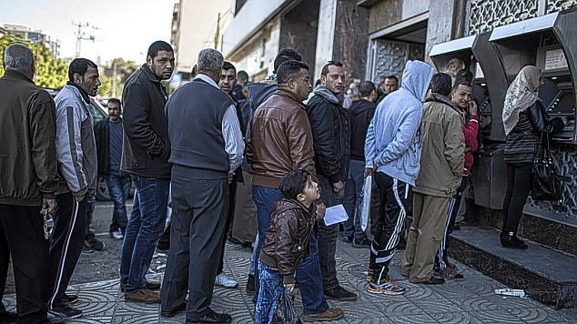 Cash for jobs that don't exist: Civil servants in Gaza are funded by western aid, who queue at cashpoints on payday (pictured), even though they haven't had jobs since 2007