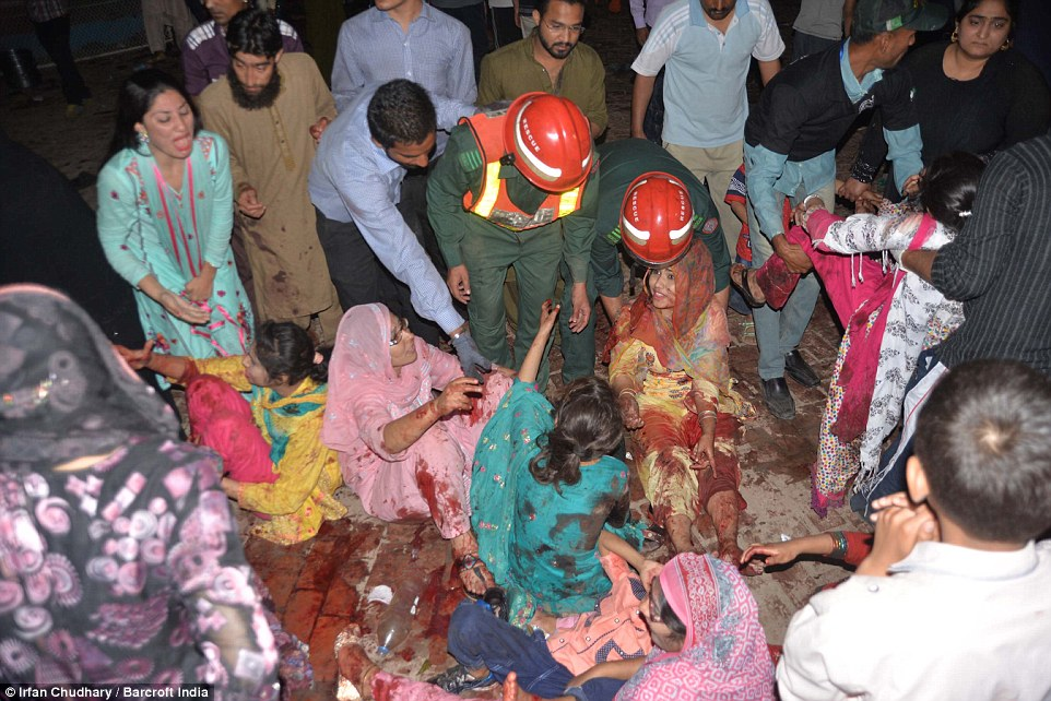 Rescuers seen helping the injured people at the explosion site, where at least 29 children lost their lives