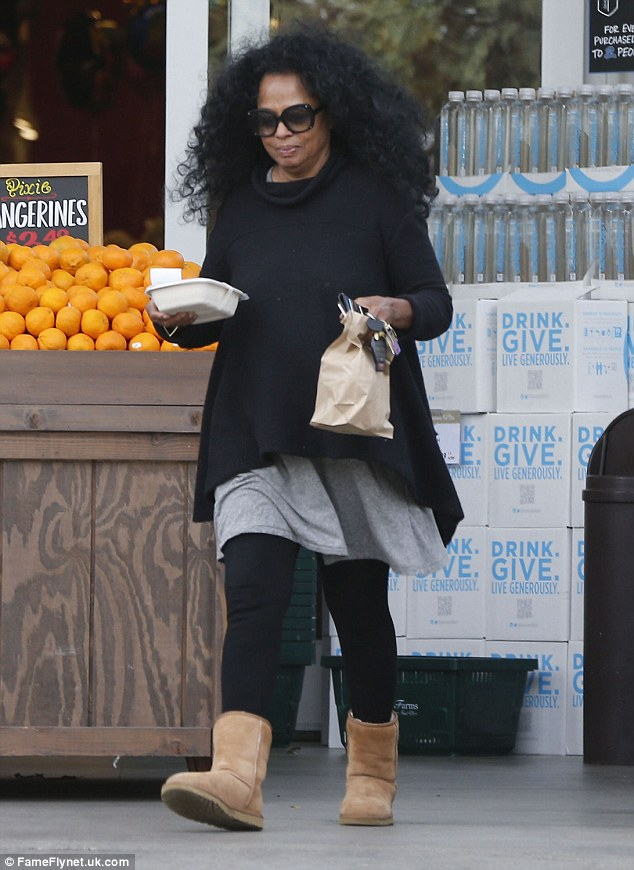 Calm and collected: She looked nice and relaxed in a comfy ensemble consisting of a baggy black jumper over a billowing grey dress which she teamed with black leggings and tan UGG boots