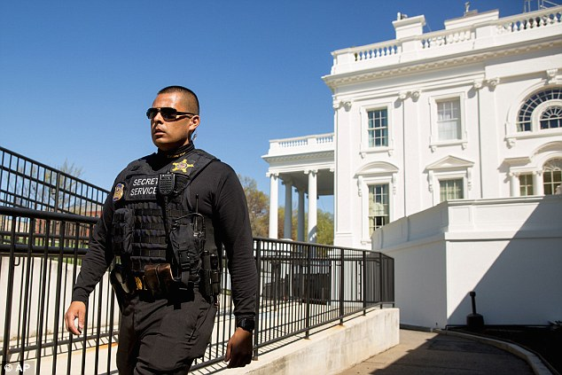 A member of the uniformed Secret Service walks near the press briefing room and the North Lawn of the White House minutes after. The White House was briefly placed on lockdown before the suspect was detained