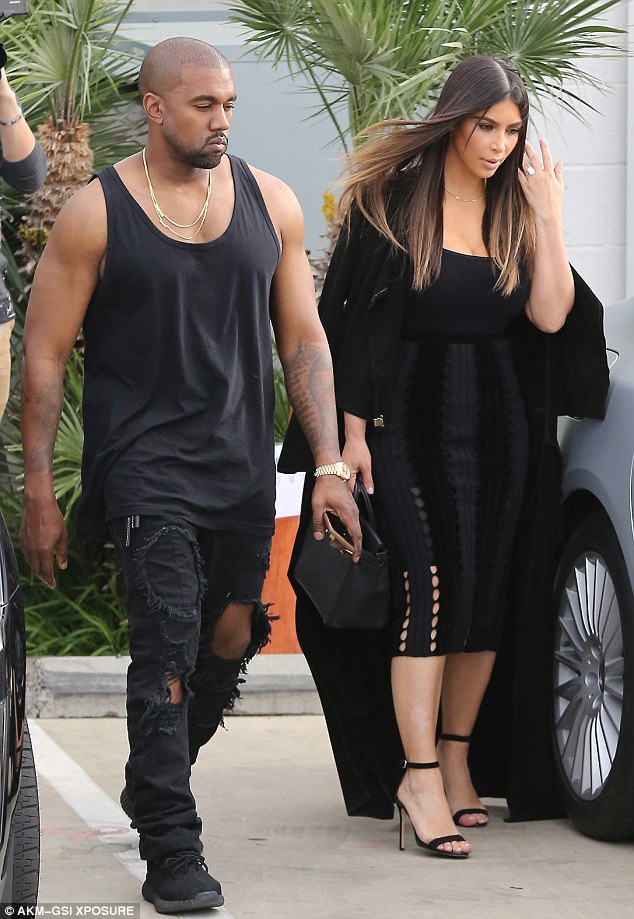 Kanye West flashed his arms while wife Kim Kardashian kept hers covered in one of her signature long coats as the duo filmed with Khloe on Monday
