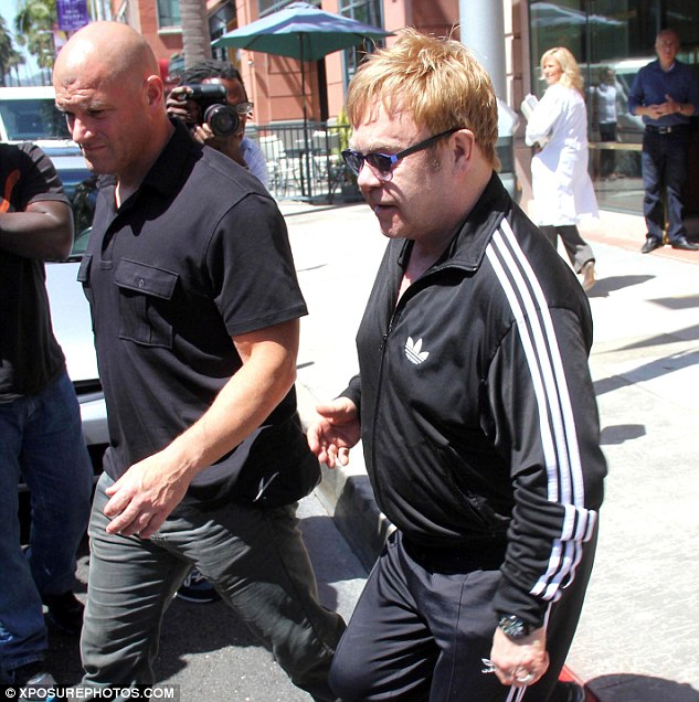 Law suit: Elton John is being sued for sexual harassment by his former bodyguard Jeffrey Wenniger, who has been identified by TMZ as the man in the left of this picture, who alleges the singer twisted his nipples and said, 'You gorgeous thing you' and also 'attempted to grab his genitals'