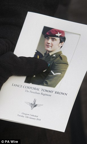 A mourners holds an order of service at the funeral of Lance Corporal Tommy Brown