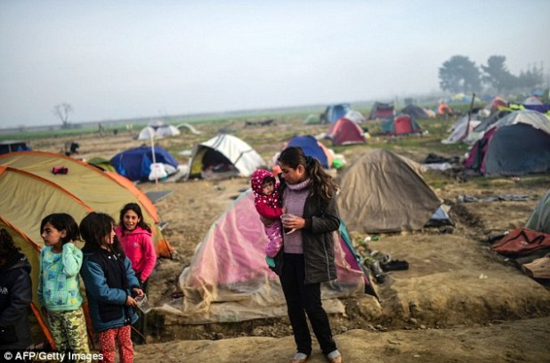 A woman carries her baby through the refugee campsite in Idomeni, Greece, where thousands hope to soon cross into Macedonia