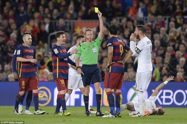 Barca striker Luis Suarez is shown a yellow card during the ill-tempered Clasico clash