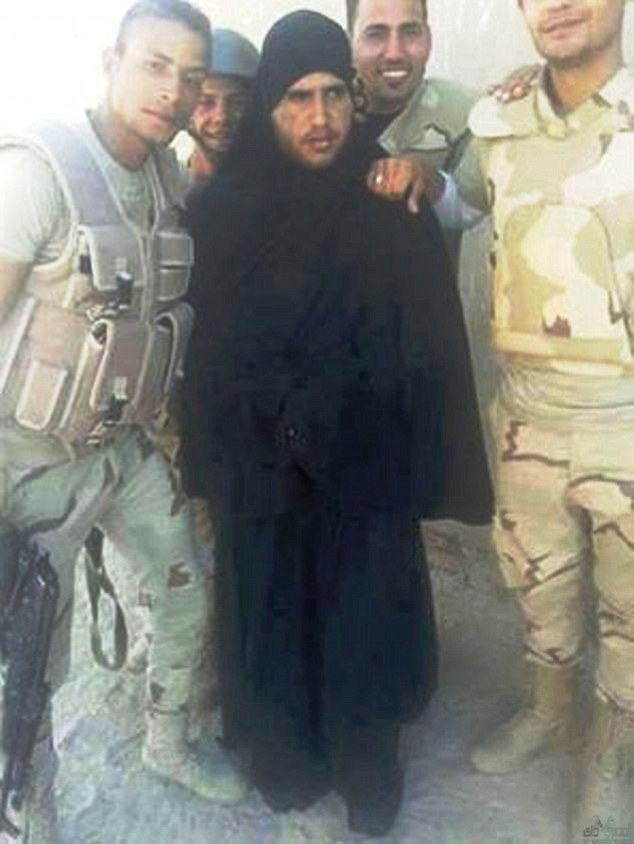 In disguise: Egyptian soldiers pose with a captured ISIS fighter dressed as a woman in a burka
